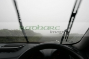 windscreen-wipers-working-on-alfa-romeo-156-car-heading-along-country-mountain-road-shrouded-in-fog-mist-IOM