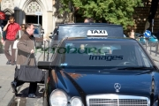 man-carries-luggage-to-open-boot-mercedes-taxi-cab-on-rank-in-krakow