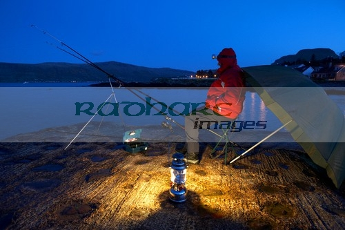 man nighttime fishing on the county antrim coast northern ireland uk