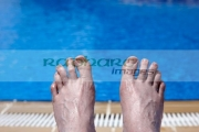 mans-feet-by-the-side-swimming-pool-on-holiday-salou-costa-daurada-spain