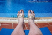 mans-feet-legs-by-the-side-swimming-pool-on-holiday-salou-costa-daurada-spain