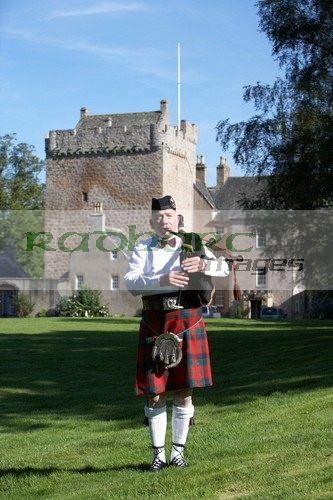 Piper playing bagpipes in front of Scottish Castle