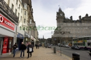 Shoppers-out-Sunday-shopping-on-Princes-Street-looking-towards-Calton-Hill,-Edinburgh,-Scotland,-UK