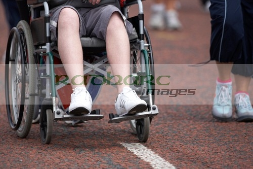 boy-in-wheelchair-being-pushed-along-road-