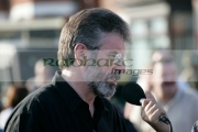 Sinn-Fein-president-MP-MLA-Gerry-Adams-talks-into-mic-on-crumlin-road-at-ardoyne-shops-belfast-12th-July