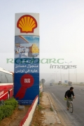 man-cycling-past-shell-garage-sign-on-highway-outside-Sousse-Tunisia-vertical