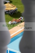 vertical-secretly-looking-out-through-balcony-down-onto-unsuspecting-sunbathing-woman-by-the-poolside-in-the-grounds-hotel