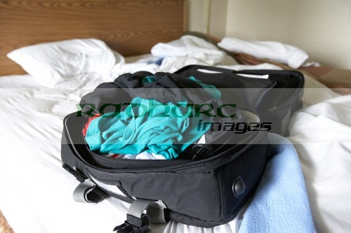 single-mans-travel-suitcase-with-bundle-clothes-on-cheap-hotel-motel-room-in-the-usa