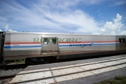 amtrack-baggage-car-on-train-crossing-road-at-train-railroad-level-crossing-near-lakefront-park-kissimmee-florida-usa